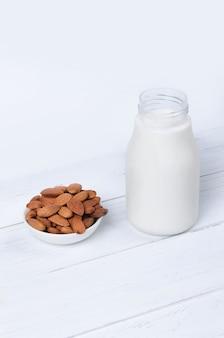 Amandelmelk in fles met noten op witte achtergrond