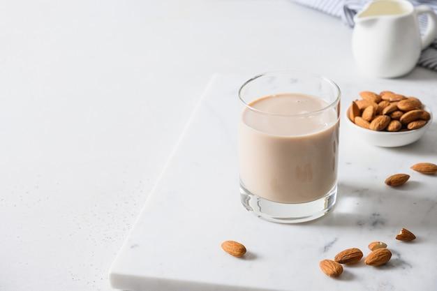 Amandelmelk in glazen fles en noten op witte achtergrond.