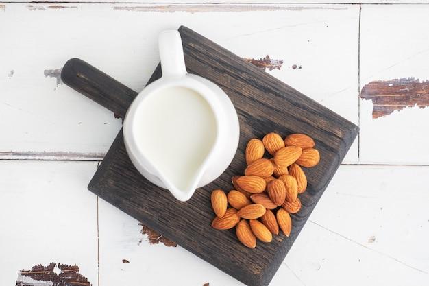 Amandelmelk in keramische melkkannetje op een grijze tafel.