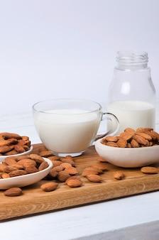 Amandelmelk in kop en fles met noten op witte muur