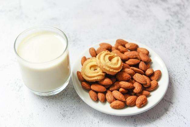 Amandelmelkglas en koekje voor ontbijtnatuurlijke voeding. amandelen noten op witte plaat achtergrond
