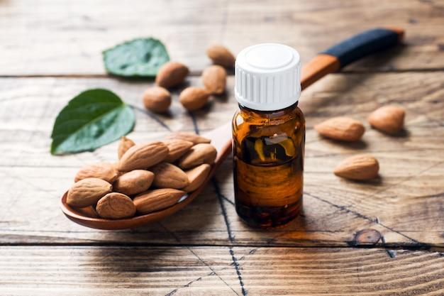 Amandelolie in fles op houten lijst. concept spa, aromatherapie en geneeskunde.