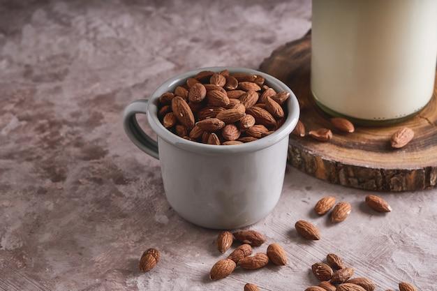 Amandelpitten en zelfgemaakte amandelmelk in fles op rustieke oppervlak. alternatief eten en drinken.