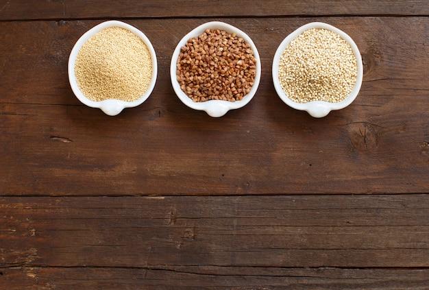 Amarant, boekweit en quinoa in kommen op een houten tafel