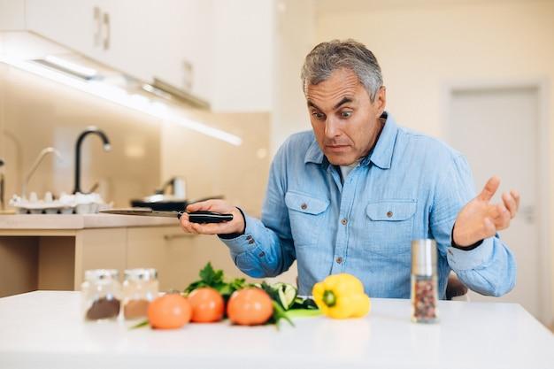 Amateur kok concept. de verbaasde volwassen man weet niet hoe hij een gerecht moet koken