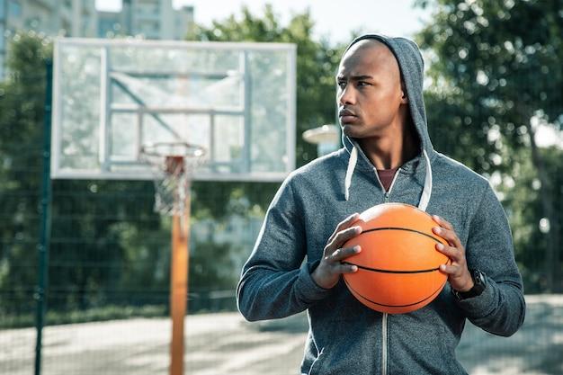 Amateur-speler. ernstige jonge man die naar het basketbalveld kijkt terwijl hij daar komt spelen