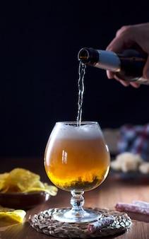 Ambachtelijk bierglas, donkere houten tafel.