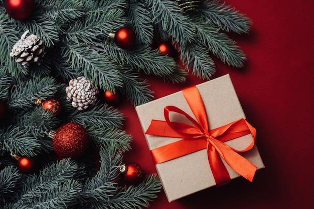 Ambachtelijk cadeau met een rood satijnen lint naast kerstboomtakken en -ballen