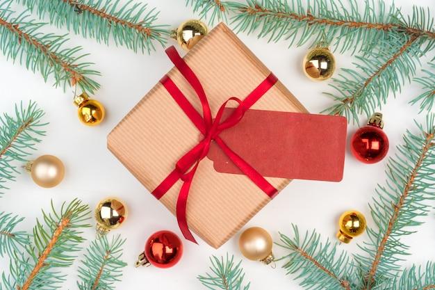 Ambachtelijk kerstcadeau omringd met pijnboomtakken en mini-kerstballen