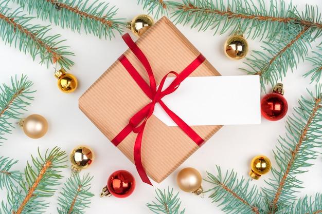 Ambachtelijk kerstcadeau omringd met pijnboomtakken en minisnuisterijen