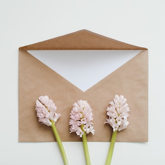 Ambachtelijk papier omhullen met witte kaart en roze hyacintbloemen op witte achtergrond