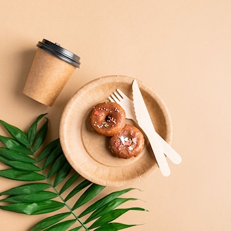 Ambachtelijk papieren bord met donuts, beker, vork en mes