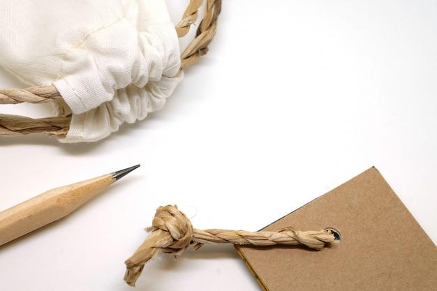 Ambachtelijk setobject, potlood, stoffen tas en papieren label, natuurlijke tinten vintage
