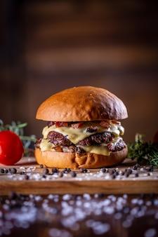 Ambachtelijke beef smash burger met kaas, spek en saus op houten achtergrond