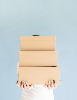 Ambachtelijke dozen in handen van de vrouw mooie glimlachende vrouw met lege dozen
