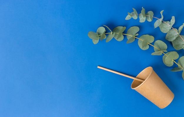 Ambachtelijke eco-beker met een papieren buis voor lekkere drankjes en eucalyptusbladeren op blauwe achtergrond.