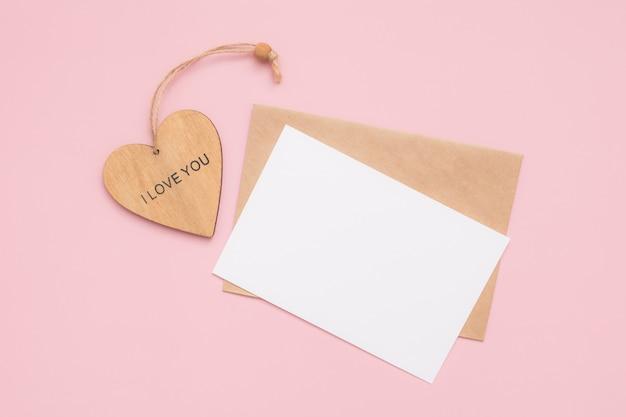 Ambachtelijke envelop, blanco papier, witte kaart en houten hart met de woorden i love you op een roze achtergrond
