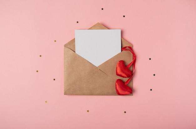 Ambachtelijke envelop met een blanco vel en rode harten op de roze achtergrond met sterren. plat lag, bovenaanzicht. romantische liefdesbrief voor valentijnsdag concept.