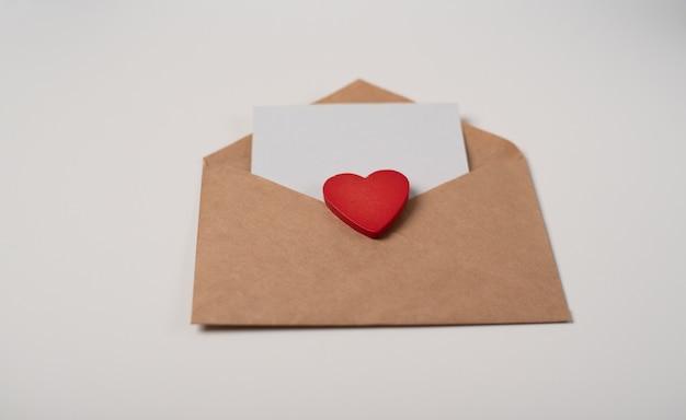 Ambachtelijke envelop met een blanco vel papier en een rood hart op de witte achtergrond. romantische liefdesbrief voor valentijnsdag concept.