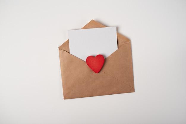 Ambachtelijke envelop met een blanco vel papier en rood houten hart op de witte achtergrond. romantische liefdesbrief voor valentijnsdag concept.