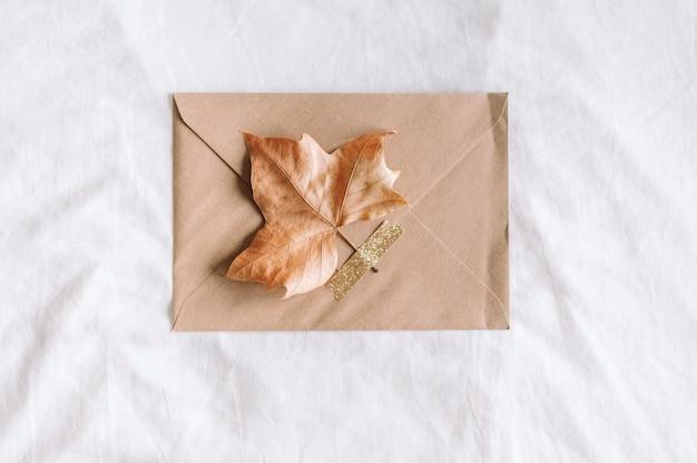 Ambachtelijke envelop met een herfstblad op witte achtergrond