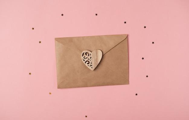 Ambachtelijke envelop met houten hart erop op de roze achtergrond met sterren. romantische liefdesbrief voor valentijnsdag concept. bovenaanzicht.