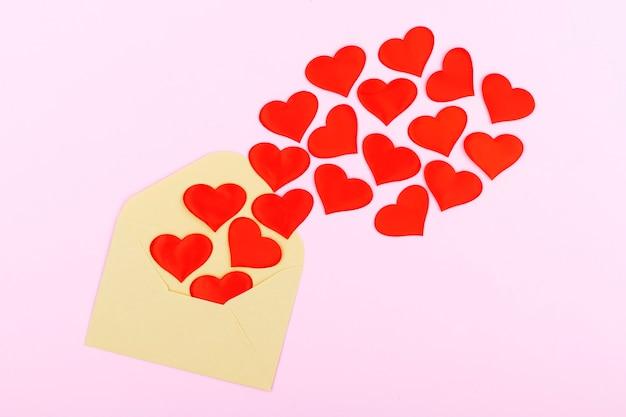 Ambachtelijke envelop met rode harten op pastel roze achtergrond. plat lag, bovenaanzicht. valentijnsdag concept. moederdag concept.