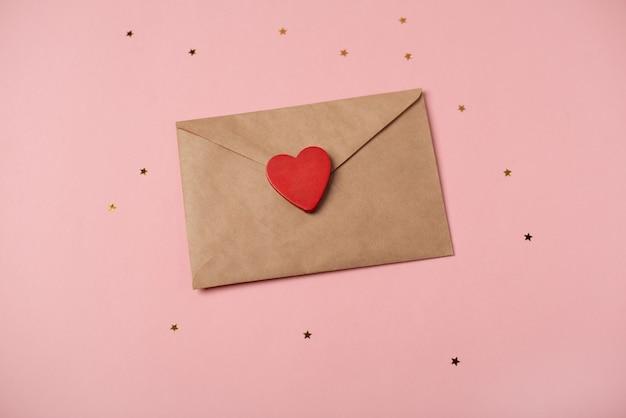 Ambachtelijke envelop met rood hart erop op de roze achtergrond met sterren. romantische liefdesbrief voor valentijnsdag concept.