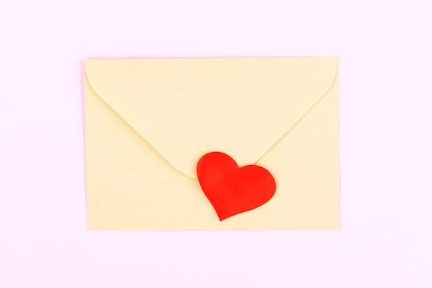 Ambachtelijke envelop met rood hart op pastel roze achtergrond. plat lag, bovenaanzicht. valentijnsdag concept. moederdag concept.