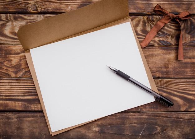 Ambachtelijke envelop, wit papier erin en zwart potlood op oude bruine houten tafel