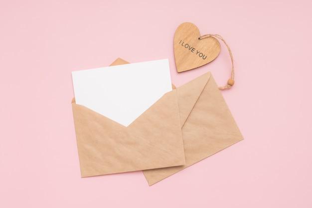 Ambachtelijke enveloppen, blanco papier, witte kaart en houten hart met de woorden i love you op een roze achtergrond