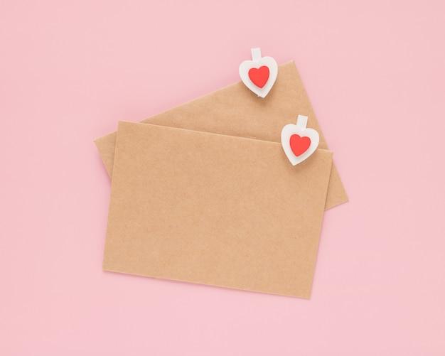 Ambachtelijke enveloppen en houten clips hartjes op een roze achtergrond. valentijnsdag concept.