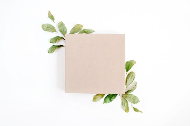 Ambachtelijke geschenkdoos en bloemensamenstelling met groene bladeren op een witte ondergrond