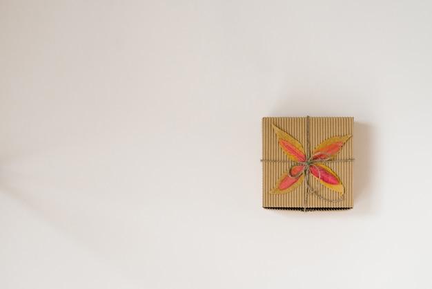 Ambachtelijke geschenkdoos, gebonden met koord met een boog en herfst gevallen bladeren