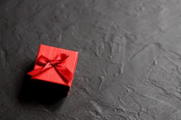 Ambachtelijke geschenkdoos op een zwarte achtergrond, versierd met een strik. voor verjaardag, jubileumgeschenken, cadeaubonnen.