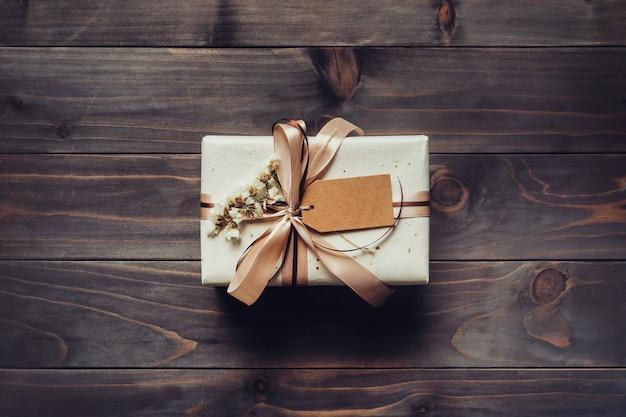 Ambachtelijke geschenkdoos op houten tafelachtergrond met kopieerruimte