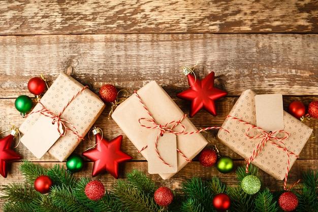Ambachtelijke geschenkdoos vastgebonden met rood en wit touw en versierd met kerst groene en rode sterren en ballen op houten tafel, bovenaanzicht