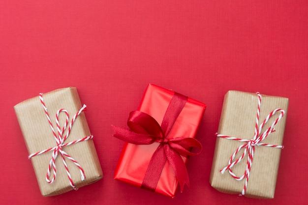 Ambachtelijke geschenkdozen op rode achtergrond. kerst mock up met kopie ruimte.