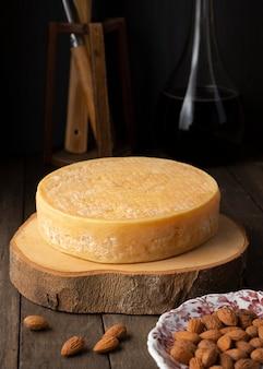 Ambachtelijke kaas en amandelen op een houten bord met wijnfles