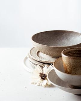 Ambachtelijke keramiek, lege ambachtelijke keramische kom, borden en beker op lichte achtergrond