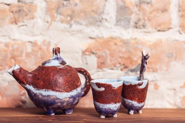 Ambachtelijke keramische theepot en kopje voor theeceremonie staande op oude houten plank tegen bakstenen muur.