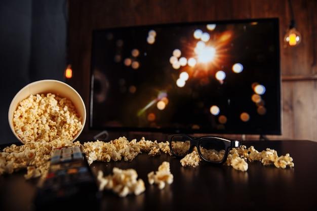 Ambachtelijke kom popcorn op de donkere tafel en tv-afstandsbediening met tv-toestel.