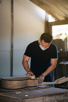 Ambachtelijke man gitaar maken op houten tafel, capenter werkconcept