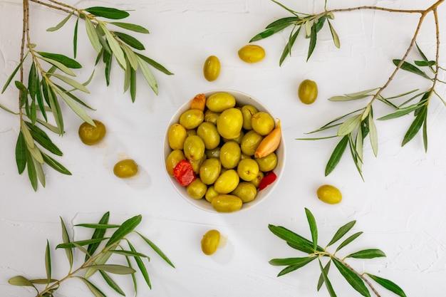 Ambachtelijke olijven (ingeblikt in extra vierge olijfolie, azijn, kruiden) met rode pepers en knoflook. voorgerecht concept.
