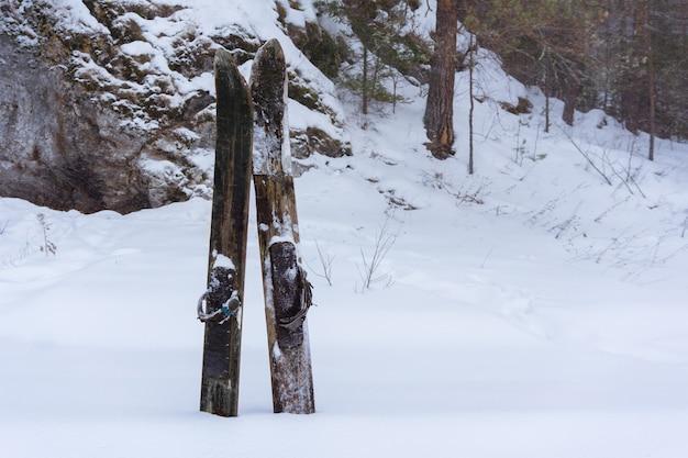 Ambachtelijke oude traditionele kapotte jachtski's vast in de sneeuw tegen het winterbos en de rots