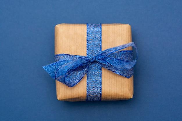 Ambachtelijke papier gewikkeld geschenkdoos geïsoleerd op blauw, plat lag, abstracte kerstcadeau.