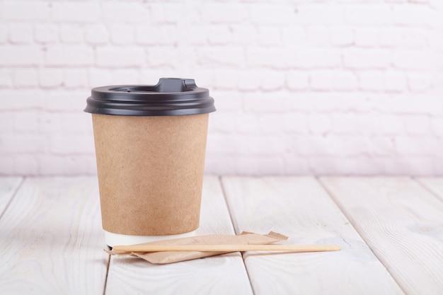 Ambachtelijke papier koffie kopjes op een witte tafel in de buurt van lichte muur achtergrond