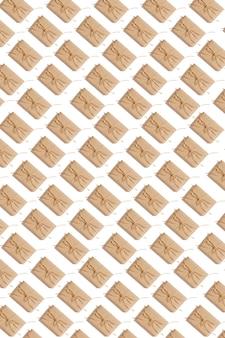 Ambachtelijke papieren huidige dozen vastgebonden van touw op witte achtergrond, bovenaanzicht. patroon. stilleven. plat leggen