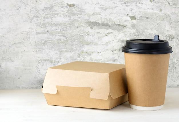Ambachtelijke papieren koffiekop en voedseldoos op tafel Premium Foto