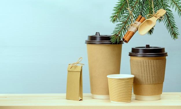 Ambachtelijke papieren koffiekopjes en papieren zak op een houten tafel met kerstversieringen op dennenboom. kerst koffie achtergrond